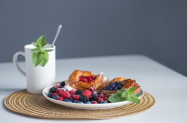 Xícara de chá com hortelã e sobremesa com frutas vermelhas
