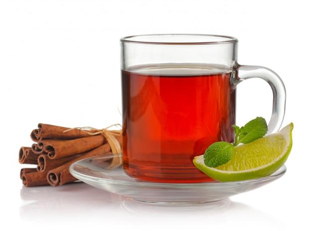 Xícara de chá com hortelã fresca, limão e canela isolado no branco