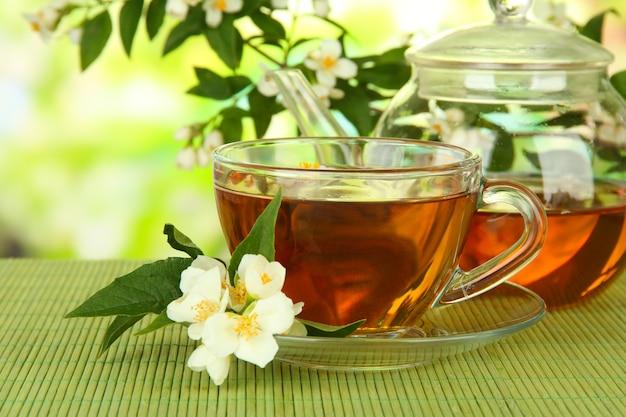 Xícara de chá com jasmim, na esteira de bambu, em fundo brilhante