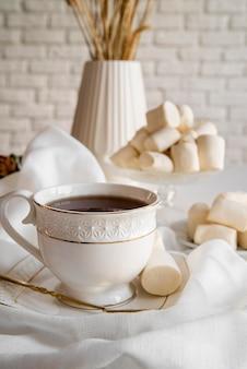 Xícara de chá com lanche ao lado