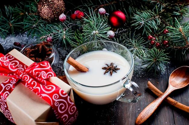 Xícara de chá com leite e canela, abeto, cones, cacau em copo vermelho sobre o fundo escuro de madeira