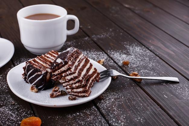 Xícara de chá com leite e duas placas com bolo de queijo e bolo de chocolate
