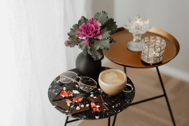 Xícara de chá com leite e óculos em uma mesa preta ao lado de uma cortina