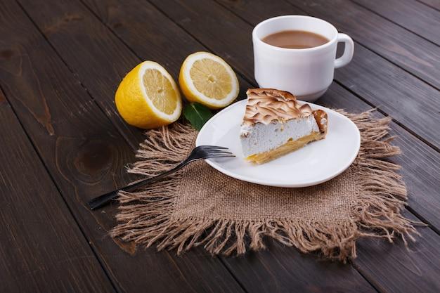 Xícara de chá com leite e pedaço de pue de limão servido na mesa de madeira escura