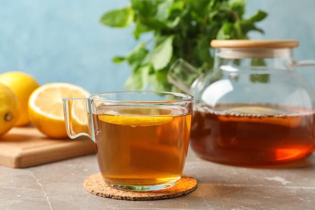 Xícara de chá com limão, bule e hortelã em cinza, close-up
