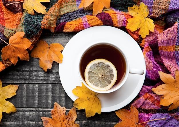 Xícara de chá com limão com cachecol e folhas de outono na superfície de madeira