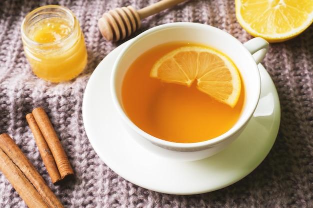 Xícara de chá com limão e biscoitos, mel e paus de canela, anis estrelado no cobertor