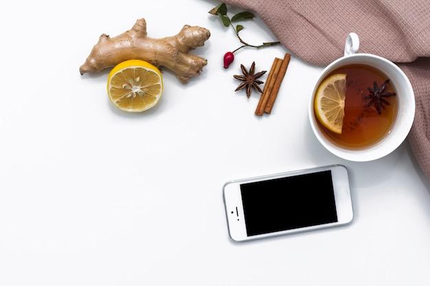 Xícara de chá com limão e gengibre perto de smartphone
