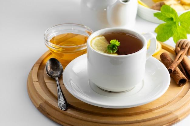 Xícara de chá com limão e mel em um branco. xícara de chá quente isolada, vista superior. bebida de outono, outono ou inverno. copyspace.