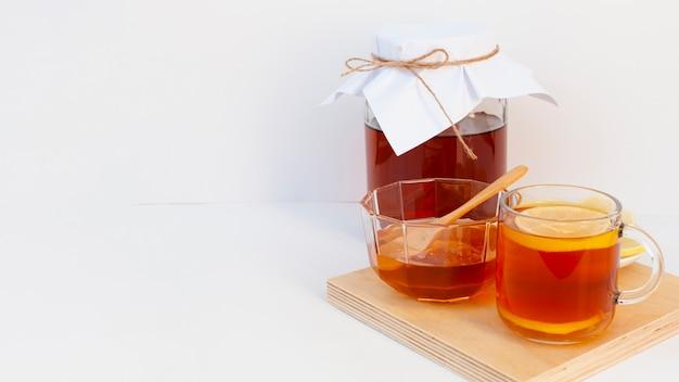 Xícara de chá com limão e uma jarra em uma placa de madeira