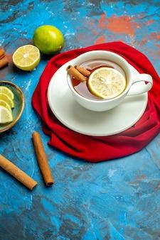 Xícara de chá com limão e xale vermelho canela na superfície azul vermelha