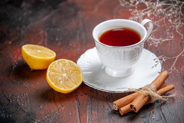 Xícara de chá com limão em fundo escuro de vista frontal
