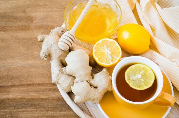 Xícara de chá com limão gengibre e mel.
