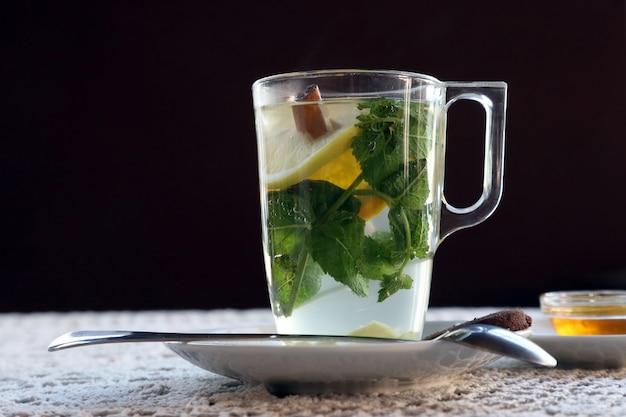 Xícara de chá com limão, hortelã, canela e sobremesa