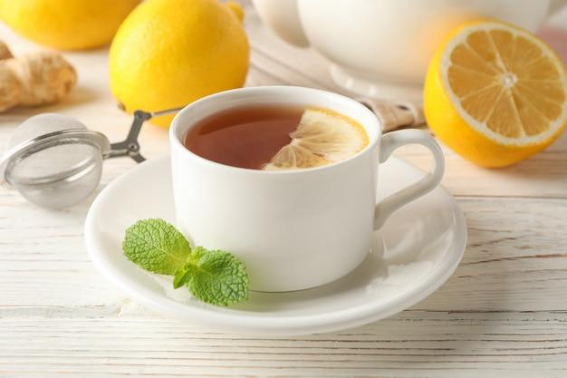 Xícara de chá com limão, hortelã, filtro, gengibre e bule de madeira, close-up