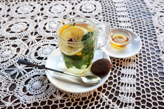 Xícara de chá com limão, hortelã, gengibre e sobremesa