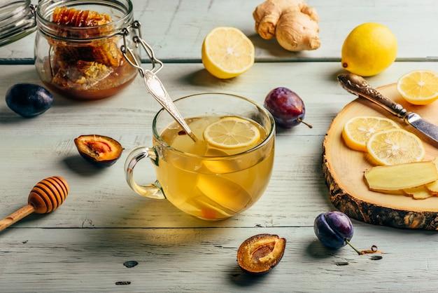 Xícara de chá com limão, mel e gengibre sobre superfície de madeira Foto Premium