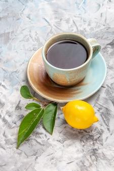 Xícara de chá com limão na mesa branca bebida chá de frutas com vista frontal