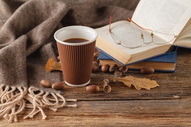 Xícara de chá com livro velho, folhas de outono na mesa de madeira