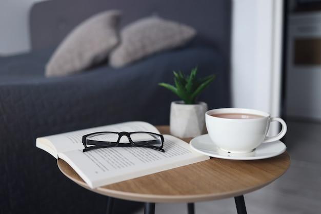 Xícara de chá com livros na mesa da sala