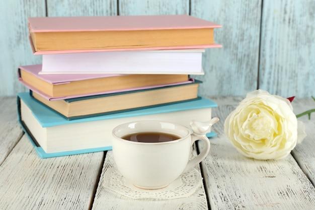 Xícara de chá com livros na mesa de madeira