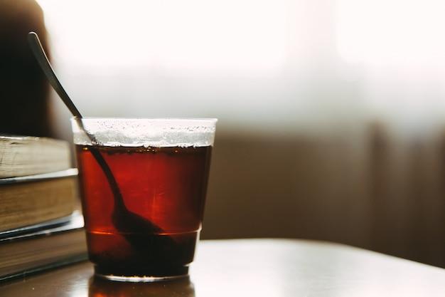 Xícara de chá com livros na mesa, foco seletivo