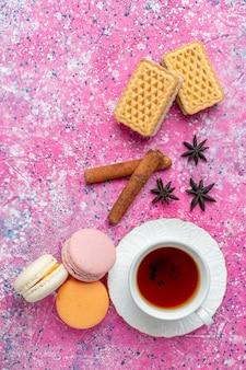 Xícara de chá com macarons franceses e biscoitos na mesa rosa claro com vista de cima