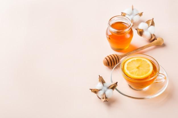 Xícara de chá com mel em um rosa pastel na moda, fundo de damasco. copie o espaço
