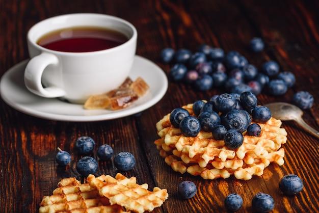 Xícara de chá com mirtilo e pilha de waffles belgas