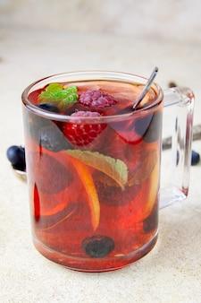 Xícara de chá com mirtilo, framboesa e hortelã