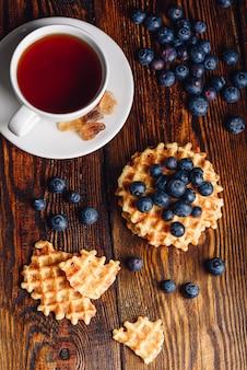 Xícara de chá com mirtilos e waffles belgas inteiros e partidos na mesa de madeira