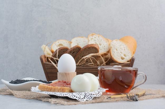 Xícara de chá com pães e ovos no saco.