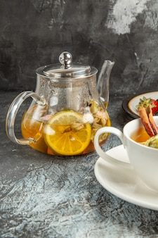 Xícara de chá com panquecas e frutas em uma superfície escura café da manhã de frente