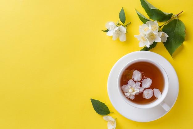 Xícara de chá com pétalas de flores de jasmim em um amarelo brilhante