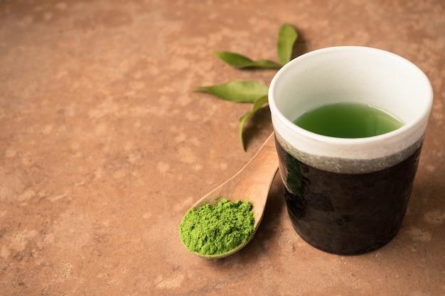 Xícara de chá com pó de chá verde na colher de pau em cima da mesa. espaço livre para o texto