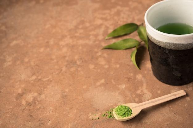 Xícara de chá com pó de chá verde na colher de pau em cima da mesa.