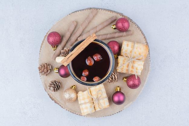 Xícara de chá com rosa mosqueta, biscoitos e enfeites na placa de madeira.