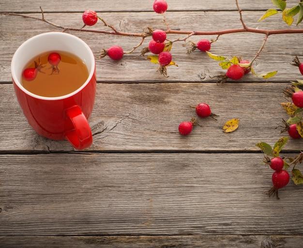Xícara de chá com rosas quadril, na mesa de madeira
