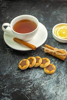 Xícara de chá com sabor de canela, fatias de limão em pequenos pires, biscoitos em palitos de canela na mesa escura