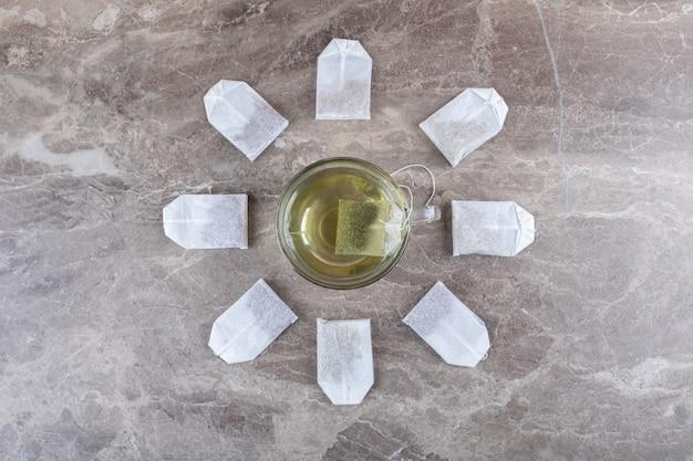 Xícara de chá com saquinhos de chá, na superfície de mármore