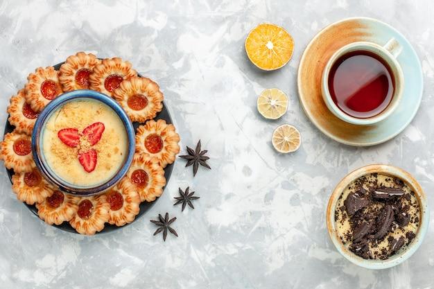 Xícara de chá com sobremesa de biscoito de chocolate e biscoitos de geleia na mesa branca clara