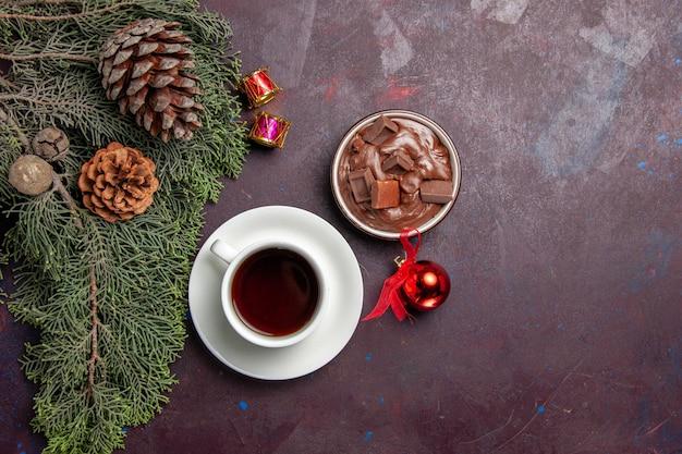 Xícara de chá com sobremesa de chocolate no espaço escuro com vista superior