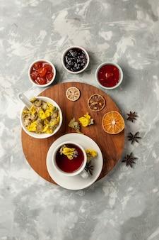 Xícara de chá com sobremesa e diferentes geleias de frutas brancas.