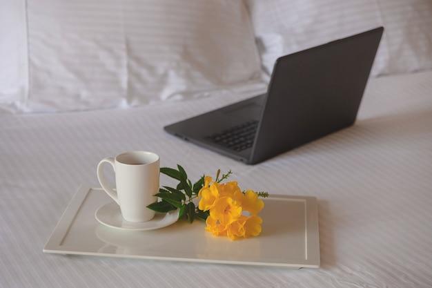 Xícara de chá com uma flor amarela em uma cama branca ao lado do laptop. local de trabalho freelancer durante a viagem