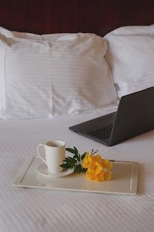 Xícara de chá com uma flor amarela em uma cama branca ao lado do laptop.