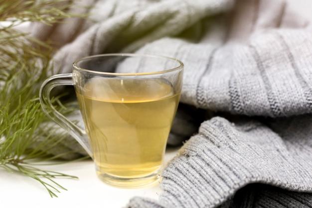 Xícara de chá com uma lã aconchegante. manhã de clima de inverno em um ambiente confortável e acolhedor.
