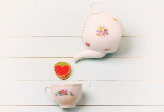 Xícara de chá cookies morangos sobre um fundo azul de madeira romântico chique gasto