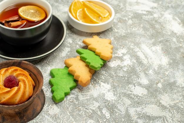 Xícara de chá de biscoitos de árvore de natal de vista inferior com canela e limão no espaço de cópia de superfície cinza