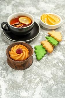 Xícara de chá de biscoitos de árvore de natal em uma superfície cinza com espaço de cópia de vista inferior