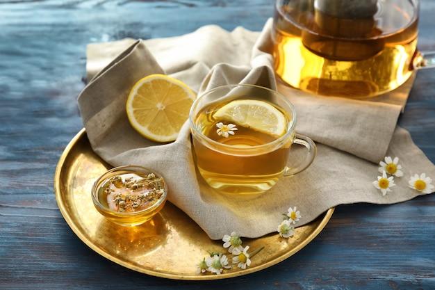 Xícara de chá de camomila delicioso e mel na mesa de madeira